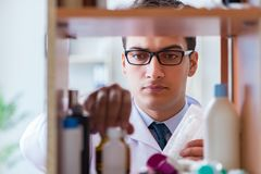 The doctor at farmacy retail shop looking for medicines. Doctor at farmacy retail shop looking for medicines Royalty Free Stock Photo