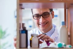 The doctor at farmacy retail shop looking for medicines. Doctor at farmacy retail shop looking for medicines Royalty Free Stock Images