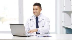 Doctor feliz con el ordenador portátil y el tablero en hospital almacen de metraje de vídeo