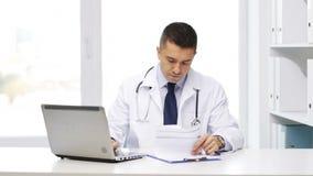 Doctor feliz con el ordenador portátil y el tablero en hospital metrajes