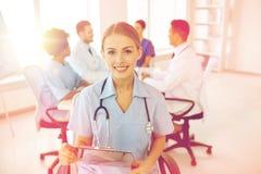 Doctor feliz con el tablero sobre el grupo de médicos Foto de archivo