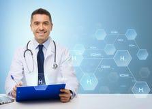 Doctor feliz con el tablero sobre fondo azul imágenes de archivo libres de regalías