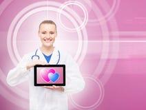 Doctor feliz con una tableta y corazones en ella Fotos de archivo