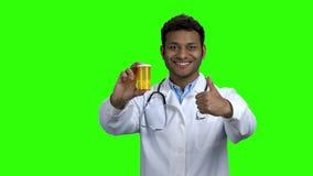 Doctor feliz que muestra píldoras y el pulgar para arriba almacen de metraje de vídeo