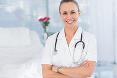 Doctor feliz que sonríe en la cámara detrás de la cama Fotografía de archivo libre de regalías
