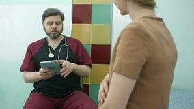 Doctor feliz que tiene un cunsultation con la mujer embarazada, usando la tableta digital almacen de video