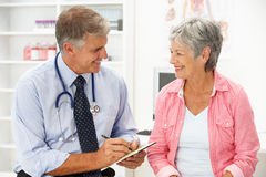 Doctor with female patient Stock Images