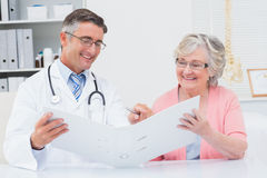 Doctor and female patient looking at reports in file Royalty Free Stock Photography