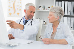 Doctor with female patient reading reports on computer Stock Photo