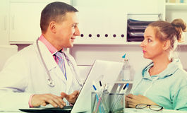 Doctor and female visitor. Female visitor consulting smiling men doctor in hospital Stock Photography