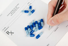 Doctor filling in empty medical prescription Stock Photography
