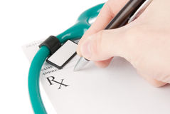 Doctor filling in empty medical prescription with stethoscope Royalty Free Stock Photography