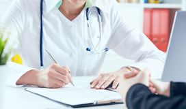 Doctor filling medical form while patient consultation. Patient sitting at doctor office. Diagnostic and prevention of women diseases, healthcare and medical Stock Photo