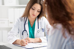 Doctor filling medical form while patient consultation. Patient sitting at doctor office. Diagnostic and prevention of women diseases, healthcare and medical Stock Image
