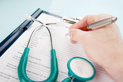 Doctor filling in medical questionnaire document Stock Photography