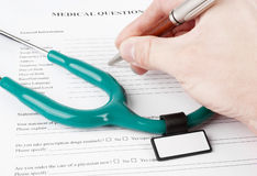 Doctor filling in medical questionnaire Stock Photo