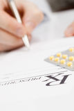 Doctor filling out drug prescription - studio shot Stock Image