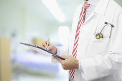 Doctor filling out medical document Stock Image