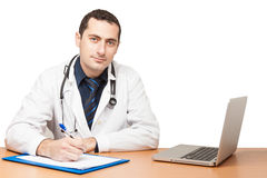 Doctor filling out medical document. Male doctor filling out medical document Stock Photos