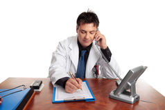 Doctor filling out patient record Royalty Free Stock Photos