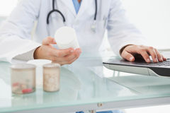 Doctor filling out prescriptions. On her laptop Royalty Free Stock Photography