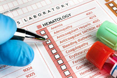 Doctor filling a request for clinical tests in medical consultat Stock Image