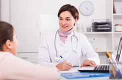 Doctor fills patient card for girl Stock Image