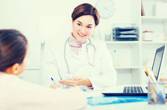 Doctor fills patient card for girl Royalty Free Stock Photos