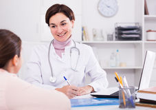 Doctor fills patient card for girl Royalty Free Stock Photo