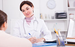 Doctor fills patient card for girl Stock Photo