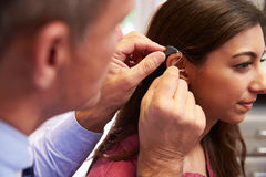 Doctor Fitting Female Patient With Hearing Aid stock photos