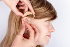Doctor fitting a young girl with hearing aid. Doctor inserting a hearing aid into ear of a young girl stock images