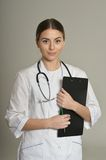 Doctor with a folder. Female doctor with a folder, standing isolated on grey background stock photos