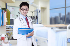 Doctor with folder in workplace Stock Photo