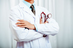 Doctor folding arms holding stethoscope Stock Images
