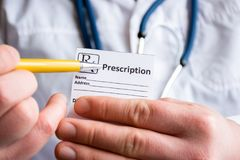 Doctor in foreground holding sample of prescription or recipe for drug, other hand indicates designation of prescription medicatio. N, which means issuing stock photos