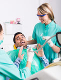 Doctor and frightened patient at clinic. Portrait of female doctor and frightened patient at dental clinic Stock Photo