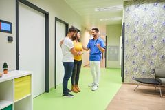 A doctor and the future parents on the hallway. A handsome male doctor consulting with a young pregnant couple while standing in the hospitals hallway stock photos