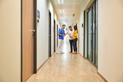 A doctor and the future parents on the hallway. A handsome male doctor consulting with a young pregnant couple while standing in the hospitals hallway royalty free stock photo