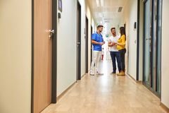 A doctor and the future parents on the hallway. A handsome male doctor consulting with a young pregnant couple while standing in the hospitals hallway royalty free stock images