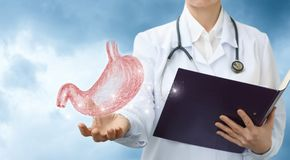 Doctor gastroenterologist shows the stomach . Doctor gastroenterologist shows the stomach against the sky stock image