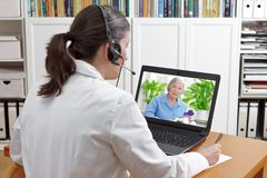 Doctor video call patient drugs. Doctor of geriatrics in her surgery office with headset in front of her laptop during a video call with a senior patient about Royalty Free Stock Photo