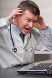 Doctor gestures in despair at laptop. Physician at desk in surgery clasps head in horror at display on laptop computer Royalty Free Stock Photo