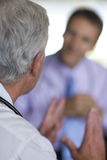Doctor gesturing and talking to co-worker Royalty Free Stock Photos