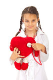 Doctor girl examine heart toy Royalty Free Stock Image