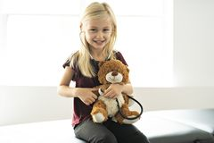A doctor girl playing and cure bear at the pediatric. Doctor girl playing and cure bear at the pediatric royalty free stock photos
