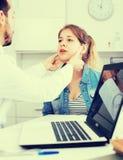 Doctor and girl with sore throat. Teenage girl with sore throat and cold visiting men doctor in hospital stock image