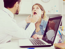 Doctor and girl with sore throat. Young female visitor having consultation about sore throat in hospital Stock Photo
