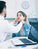 Doctor and girl with sore throat. Young female visitor having consultation about sore throat in hospital Stock Photography