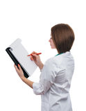 Doctor girl standing sideways and writes on the tablet. Stock Photography